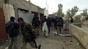 Security forces are seen at a suicide bomb blast site in Bannu, northwest Pakistan, 10 December, 2012