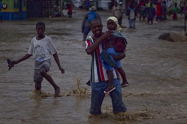 Homem atravessa rua alagada em Leogane. O furacão Tomas deixou três mortos na região.