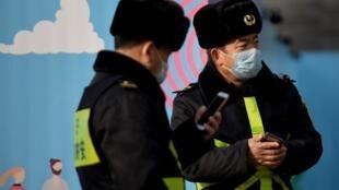 Des officiers de police portant un masque à Pékin. La Cité interdite de Pékin a annoncé sa fermeture pour éviter tout risque de contamination entre les visiteurs, et les festivités du Nouvel An lunaire ont été annulées dans la capitale chinoise.