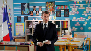 French President Emmanuel Macron arrives inside a classroom prior to attend an one-hour interview with French news channel TF1, at a school in Berd'huis, France, April 12, 2018.