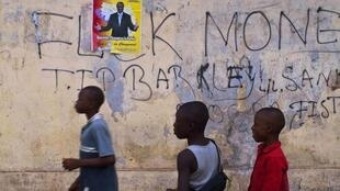 Children walk past a poster for Guinea presidential candidate Alpha Conde in Conakry, Guinea