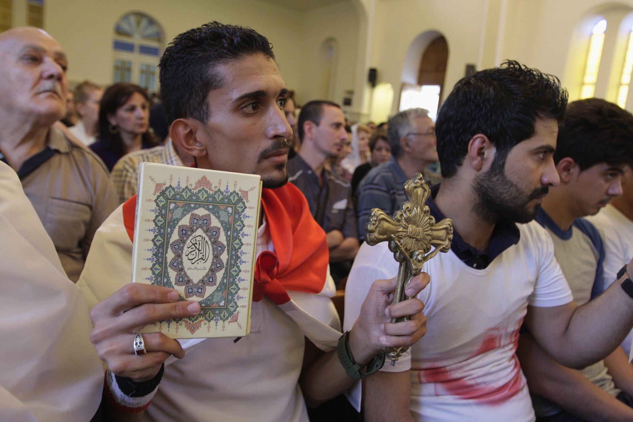 Un Irakien, dans une église de Bagdad, un coran et une croix chrétienne à la main, le 20 juillet dernier.