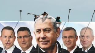 Varios obreros cuelgan un afiche de campaña del Primer Ministro israelí, Benjamín Netanyahu. Jerusalén, 28 de marzo de 2019.