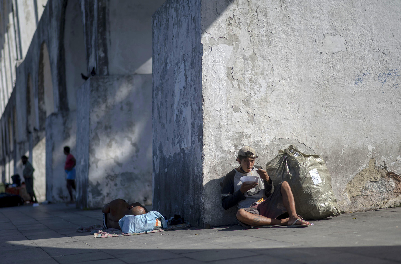 Un hombre sin hogar come alimentos que le dio el proyecto Covid Sem Fome (Covid Sin Hambre) en los Arcos de Lapa, en el centro de Río de Janeiro, Brasil, el 5 de mayo de 2021
