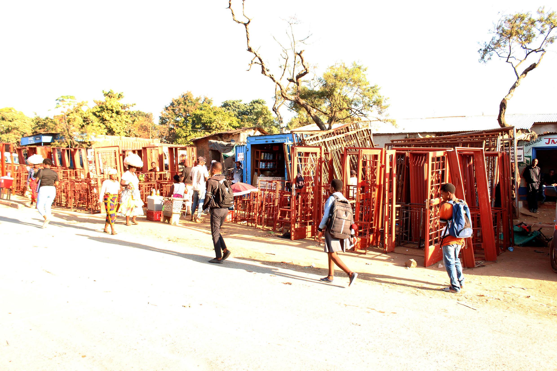 Schoolchildren pass in front of Gift Kamkwamba's metal doorframe shop in Blantyre, Malawi