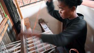 Une jeune femme sur un métier à tisser en bois travaille le raphia dans une entreprise basée à  Madagascar.
