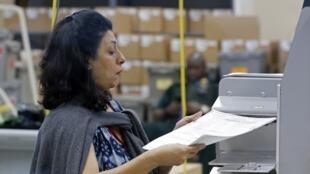 Une employée utilise une machine de décompte des voix au bureau de supervision des élections du comté de Broward, à Lauderhill en Floride, le 10 novembre 2018.