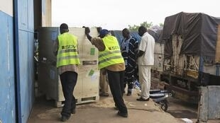 Des hommes transportent du matériel électoral provenant de France dans des bureaux de stockage à Bamako, le 18 juin 2013.