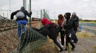 Migrants make their way across a fence near near train tracks as they attempt to access the Channel Tunnel in Frethun, near Calais, France, July 29, 2015.