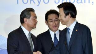 Os ministros das Relações Exteriores do Japão, Fumio Kishida (esq), da China, Wang Yi (centro), e da Coreia do Sul, Yun Byung-Se (dir), tiveram um encontro trilateral em Tóquio, na terça-feira (23).