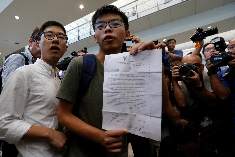 香港占中运动学生领袖之一,香港众志秘书长黄之锋(中)2016年10月5日自泰国曼谷抵达香港机场时,向媒体展示泰国海关拒绝他入境的通知信函。