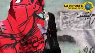 Une Iranienne portant un masque et des gants marche devant un graffiti à Téhéran, le 13 avril 2020.