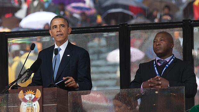 Rais wa Marekani Barack Obama akihutubia, kulia ni Mkalimani Thamsanga Dyantyi anayelalamikiwa kutumia ishara potofu kutafsiri