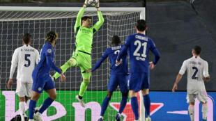 El portero belga del Real Madrid, Thibaut Courtois, ataja el remate de una jugada del Chelsea en el partido de ida por semifinales de la Champions empatado 1-1 en el estadio Alfredo di Stefano de Valdebebas, el 27 de abril de 2021
