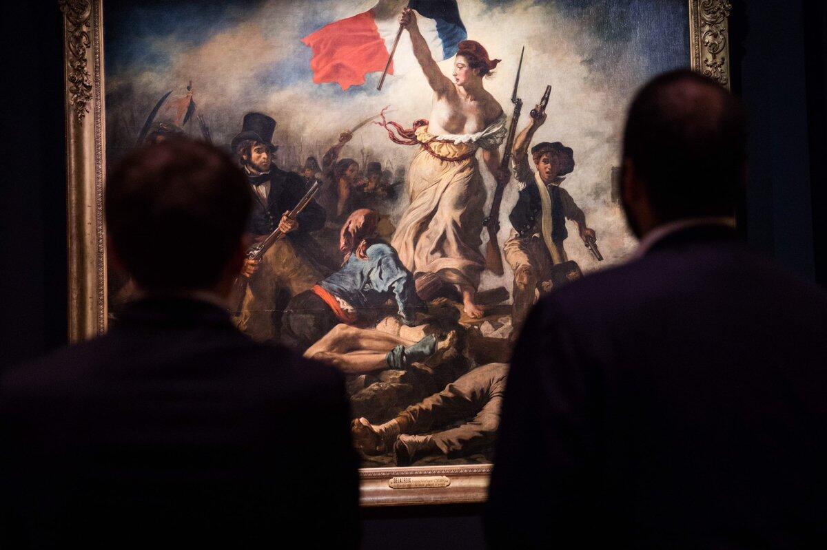 """امانوئل ماکرون، رئیس جمهوری فرانسه محمد بن سلمان ولیعهد عربستان در مقابل تابلوی معروف """"آزادی، هدایتگر ملت"""" اثر """"اوژن دُلاکروا"""" نقاش فرانسوی در موزه لوور پاریس. مانوئل ماکرون عکسی را هنگام بازدید از تابلو توئیت کرده است."""