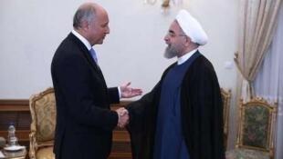 Laurent Fabius (esq), ministro francês dos Negócios Estrangeiros e Hassan Rohani (drt), presidente do Irão
