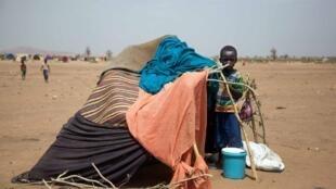 Un enfant soudanais se tient devant son abri au camp de Kalma (sud-Darfour) de l'ONU, le 9 mars 2014.