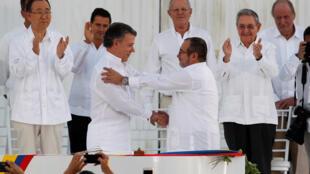 Juan Manuel Santos, Presidente da Colômbia, e Rodrigo Londoño, chefe das Farc, cumprimentam -se após a assinatura do acordo de Paz, em Cartagena