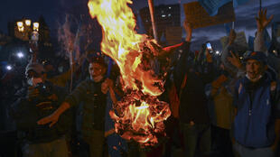 Demonstrators burn an effigy representing Guatemalan President Alejandro Giammattei during a protest demanding his resignation, in Guatemala City on November 22, 2020