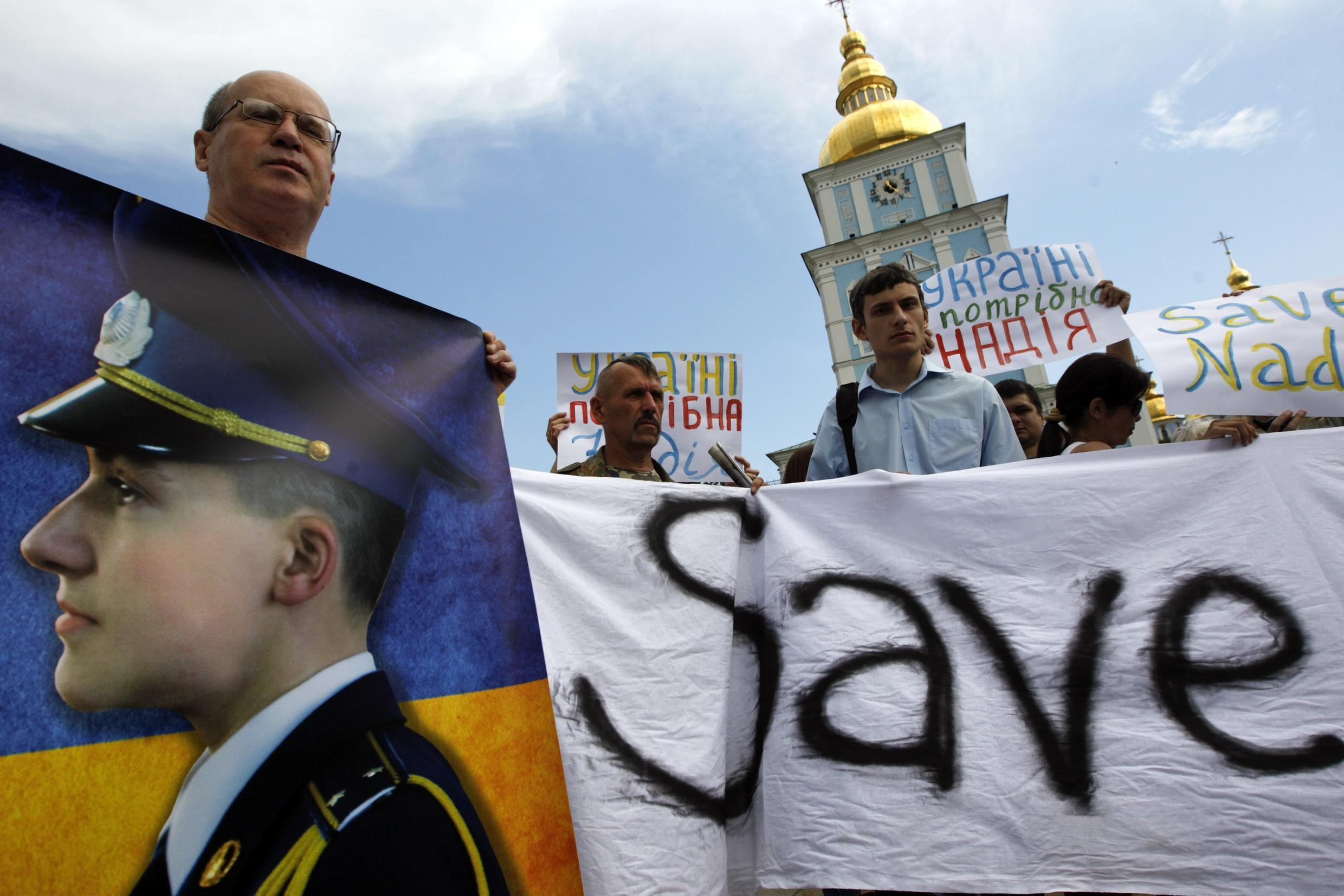 Activists hold placards and banners demanding the release of Ukrainian woman pilot, Nadezhna Savchenko, during a protest in Kiev July 11, 2014.