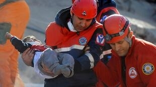 A rescue worker carries a boy to an ambulance after his team found him alive in a collapsed building in Ercis