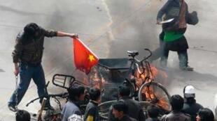 Un activiste tibétain brûle un drapeau chinois, lors d'une manifestation pour l'indépendance du Tibet, à Lhassa, le 14 mars 2008.