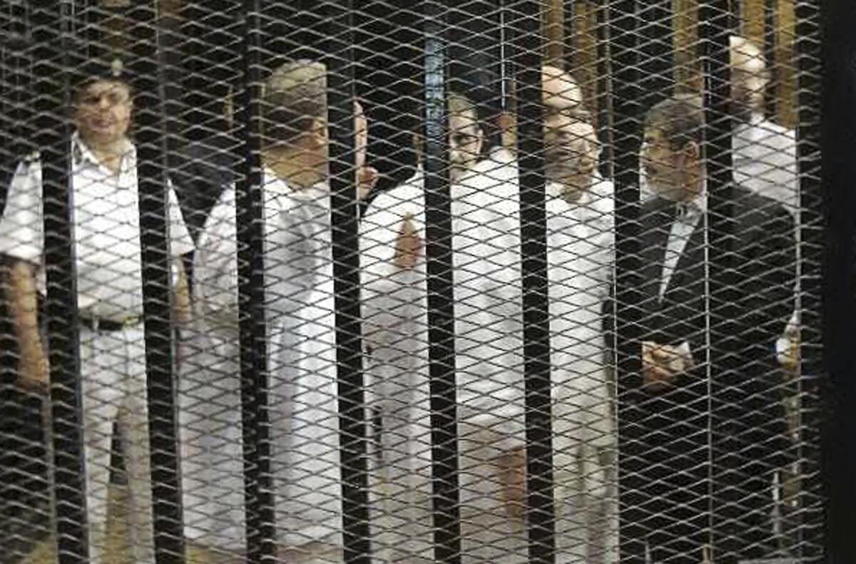 Cựu Tổng thống Ai Cập bị lật đổ Mohamed Mursi (Áo đen), nói chuyện với các lãnh đạo khác của Huynh Đệ Hồi Giáo tại phiên tòa, Cairo, 04/11/2013