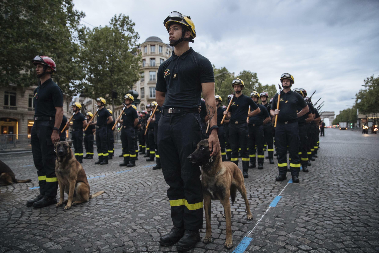 Пожарные с собаками на репетиции военного парада на Елисейских полях в Париже 9 июля 2021 г.