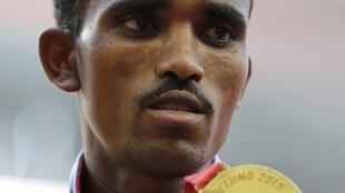 Ghirmay Ghebreselassie of Eritrea presents his gold medal after winning the men's marathon race during the 15th IAAF World Championships in Beijing, August 22, 2015.