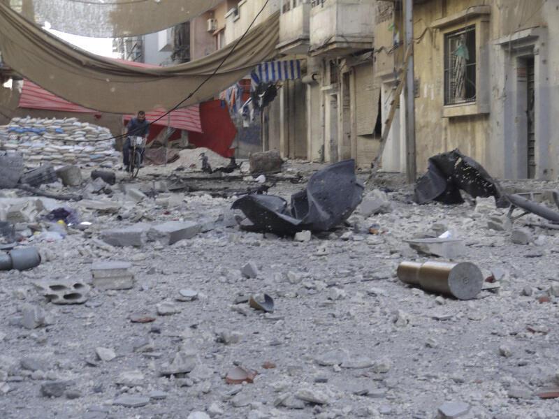 Sírio pedala na paisagem devastada do centro de Homs, em foto do dia 3 de junho.