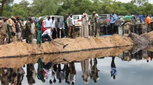 Le ministre du Pétrole (chemise rayée et lunettes de soleil) visite un forage de pétrole.
