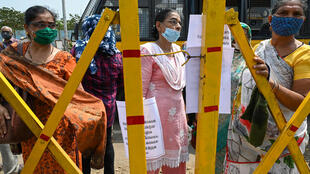 People in Mumbai stand behind a barrier outside a Covid-19 coronavirus vaccination centre after jabs were stopped due to shortage