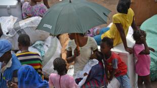 Une femme rentrée de Brazzaville lors de l'opération « Mbata ya bakolo », attend avec ses enfants au beach de Ngobila, le port de Kinshasa.