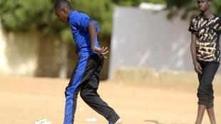 Deux adolescents sénégalais jouent au football après l'école à Dakar, le 7 décembre 2015.