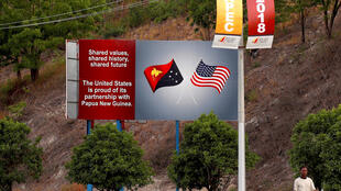 A man walks past a billboard displaying the national flags of the United States and Papua New Guinea a day after the Asia Pacific Economic Cooperation (APEC) forum ended, in Port Moresby, Papua New Guinea, November 19, 2018.