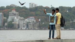 Des jeunes étudiants indiens prennent un selfie sur la promenade Marine Drive à Bombay.