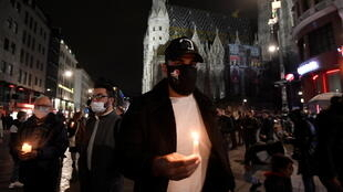 Gente sostiene velas en el exterior de la catedral de San Esteban, después de una misa religiosa por las víctimas de un atentado terrorista en Viena, Austria, el 3 de noviembre de 2020.