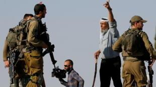 Un homme s'adresse à des soldats israéliens pendant une manifestation de colons israéliens, près de Hébron, en juin 2021.
