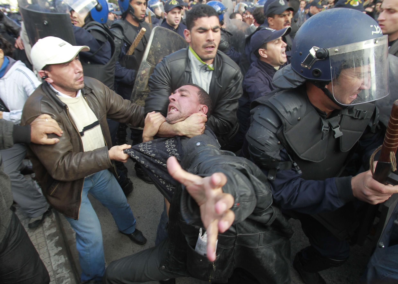 Un manifestant est interpellé brutalement par des policiers en civil, lors d'une manifestation à Alger, le 12 février 2011.