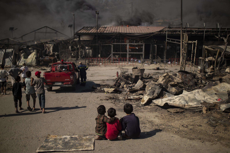 Tres niños sentados en el suelo observan una construcción del campo de Moria, en la isla de Lesbos, tras un incendio, el 9 de septiembre de 2020