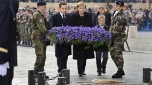 Angela  Merkel et Nicolas Sarkozy déposent une gerbe sur la tombe du soldat inconnu sous l'Arc de Triomphe à Paris, le 11 novembre 2009.