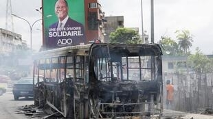 La carcasse d'un bus calciné brûlé lors de heurts survenus à Abidjan, le 19 octobre 2020.