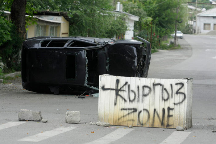 """A concrete block with a sign reading """"Kyrgyz Zone"""" in the middle of a street in Osh"""