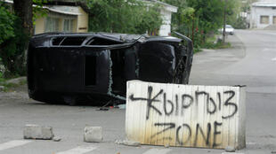 "A concrete block with a sign reading ""Kyrgyz Zone"" in the middle of a street in Osh"