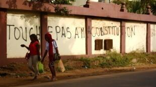 Deux femmes passent devant une inscription laissée par les opposants à une réforme de la Constitution, à Conakry.