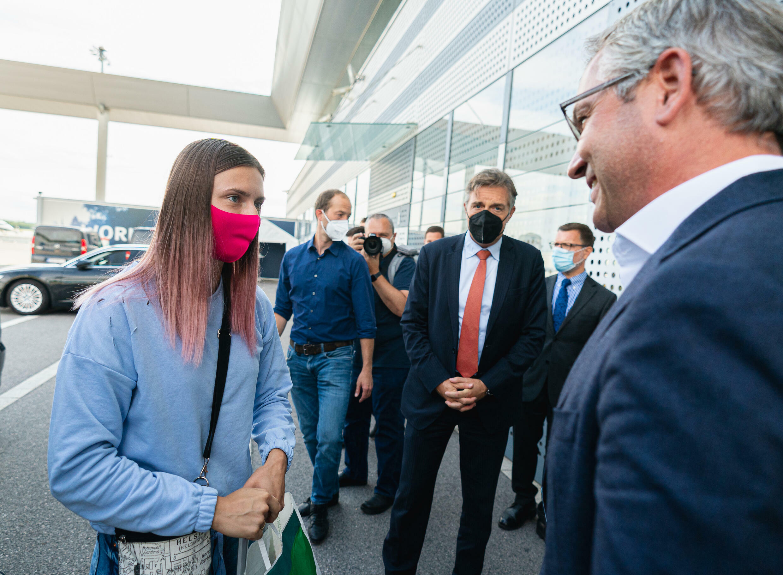 La atleta olímpica bielorrusa Krystsina Tsimanouskaya (izq.) conversa con el secretario de Estado austríaco Magnus Brunner (der.) después de su llegada al aeropuerto de Viena en Schwechat, Austria, el 4 de agosto de 2021.