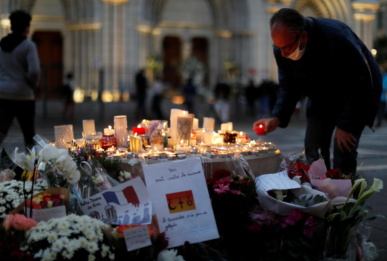 Цветы и свечи у базилики Нотр-Дам в Ницце, где в теракте погибли трое человек