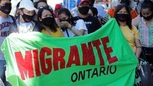 Un rassemblement de migrants, réfugiés, travailleurs sans papiers et leurs sympathisants devant le bureau du ministre de l'Immigration du Canada, à Toronto, le 4 juillet 2020.