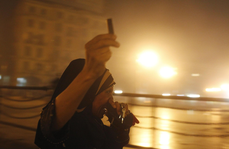 Une femme, pro-Morsi, brandit une cartouche vide après les émeutes entre les manifestants et la police au Caire.