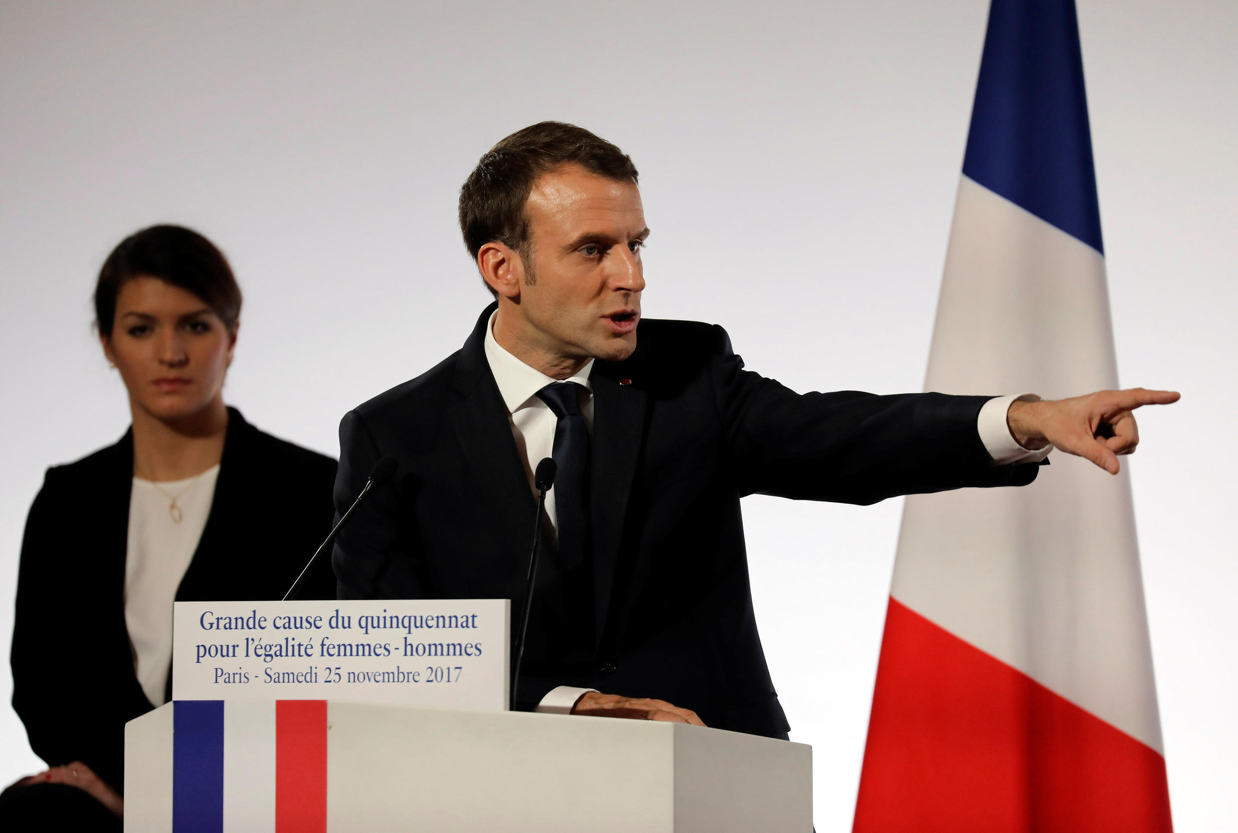 French President Emmanuel Macron delivers a speech on the International Day for the Elimination of Violence Against Women with Women's Rights Minister Marlène Schiappa listening